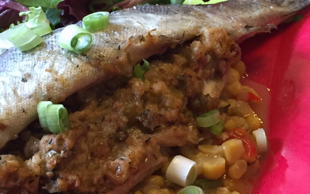 Whole roasted trout stuffed with oyster dressing and served over a creamed corn succotash
